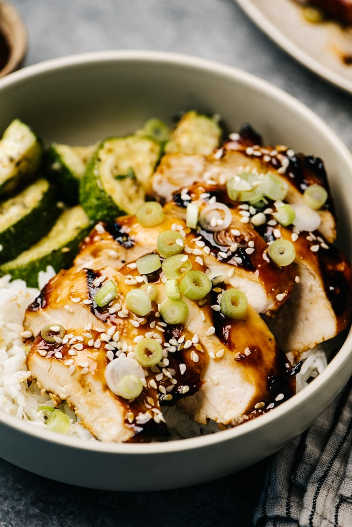 Side view, sliced of grilled teriyaki chicken over white rice in a tan bowl.