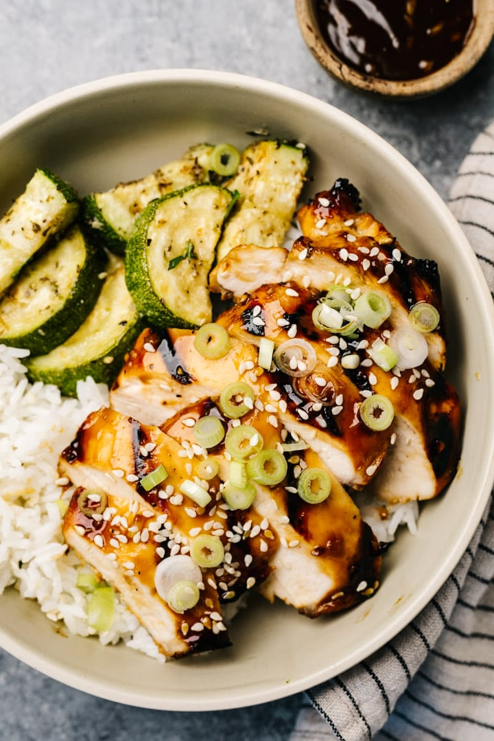 Slices of grilled teriyaki chicken over white rice and sautéed zucchini, garnished with green onions and sesame seeds.