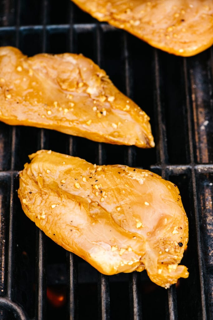 Teriyaki marinated chicken breasts on a grill.