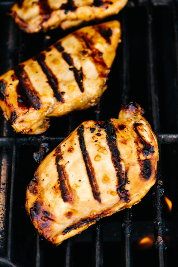 Grilled teriyaki chicken breasts on a grill.