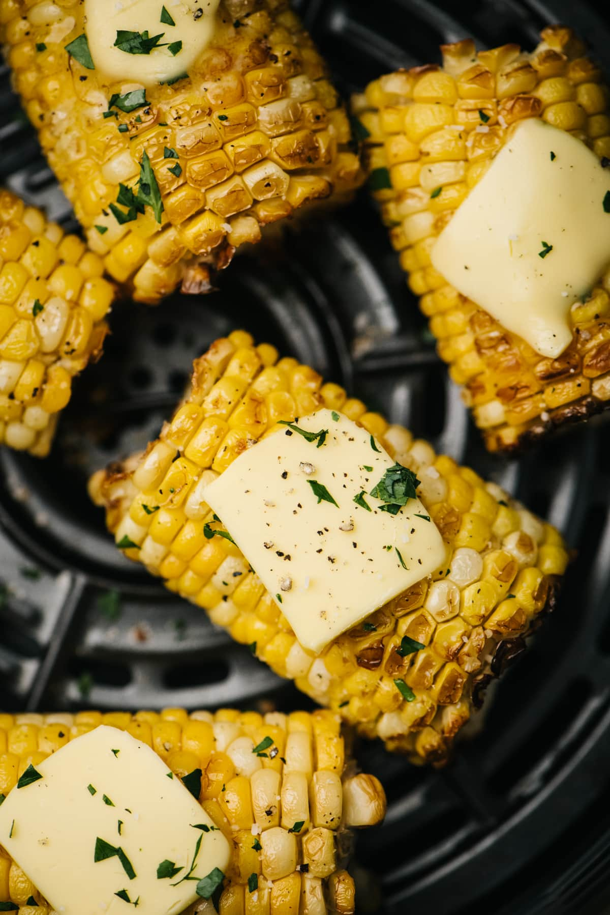 Air fryer corn on the cob topped with butter in the basket of an air fryer.
