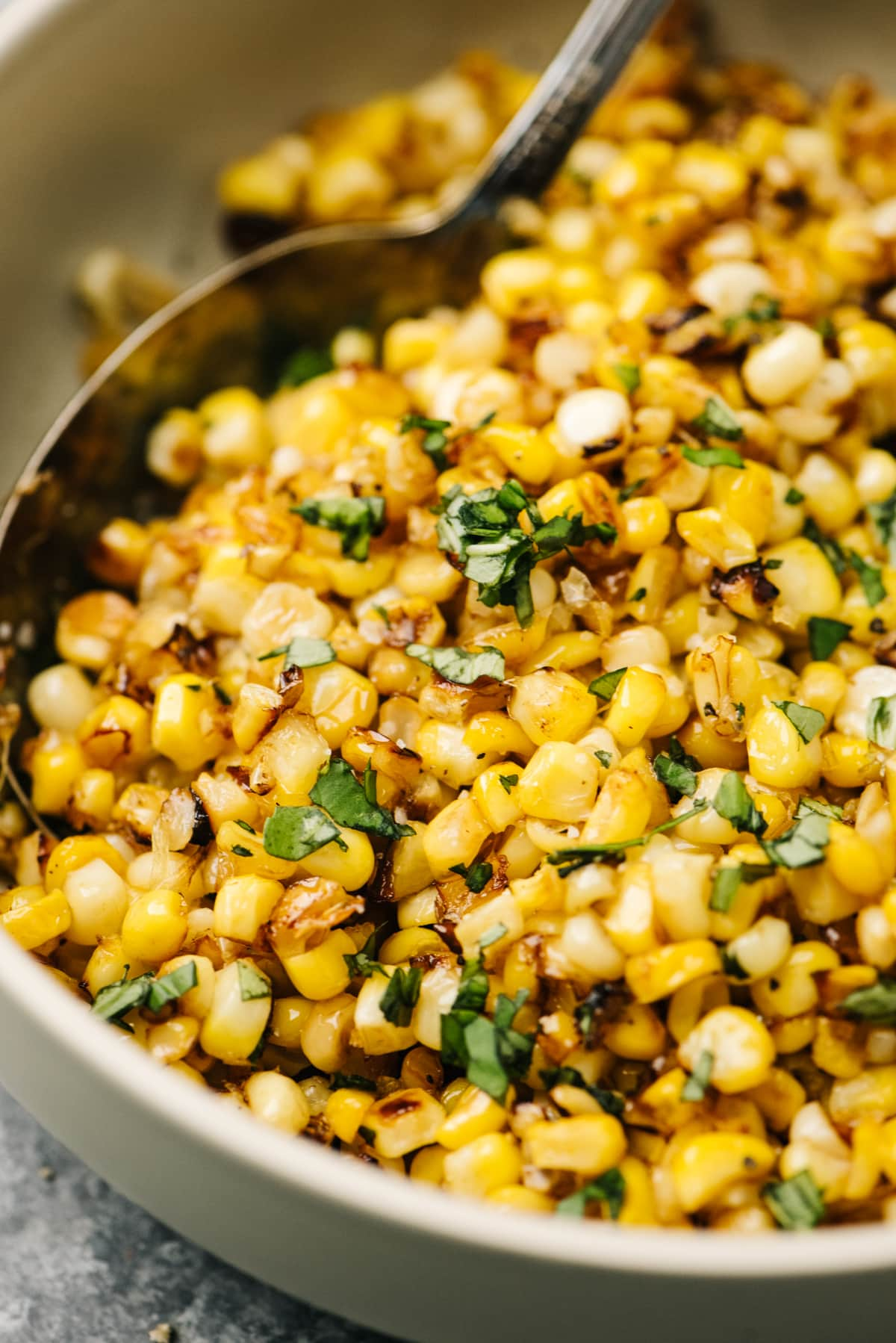 Side view, sauteed fresh corn in a tan bowl with fresh herbs and silver serving spoohn.