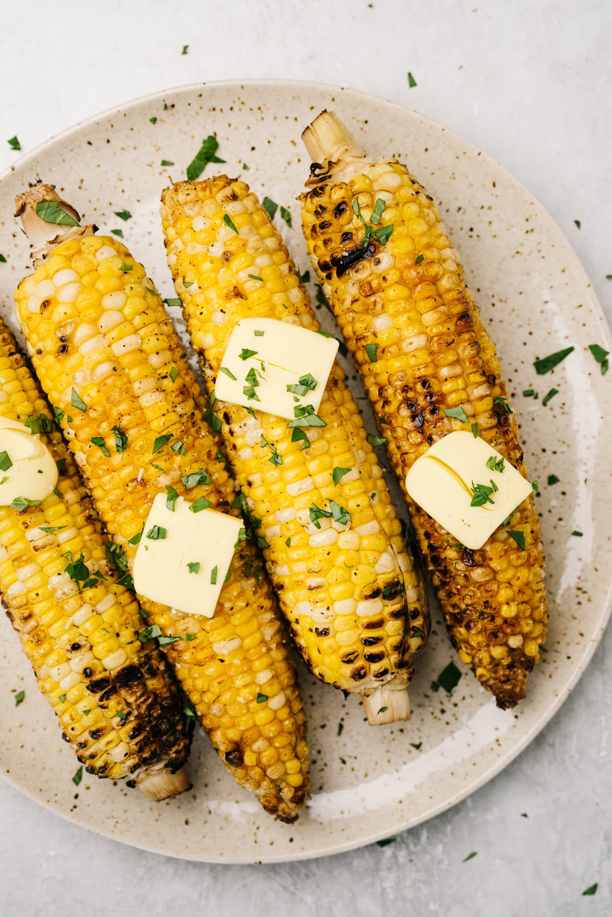 Four ears of charred grilled corn topped with butter on a speckled tan plate.