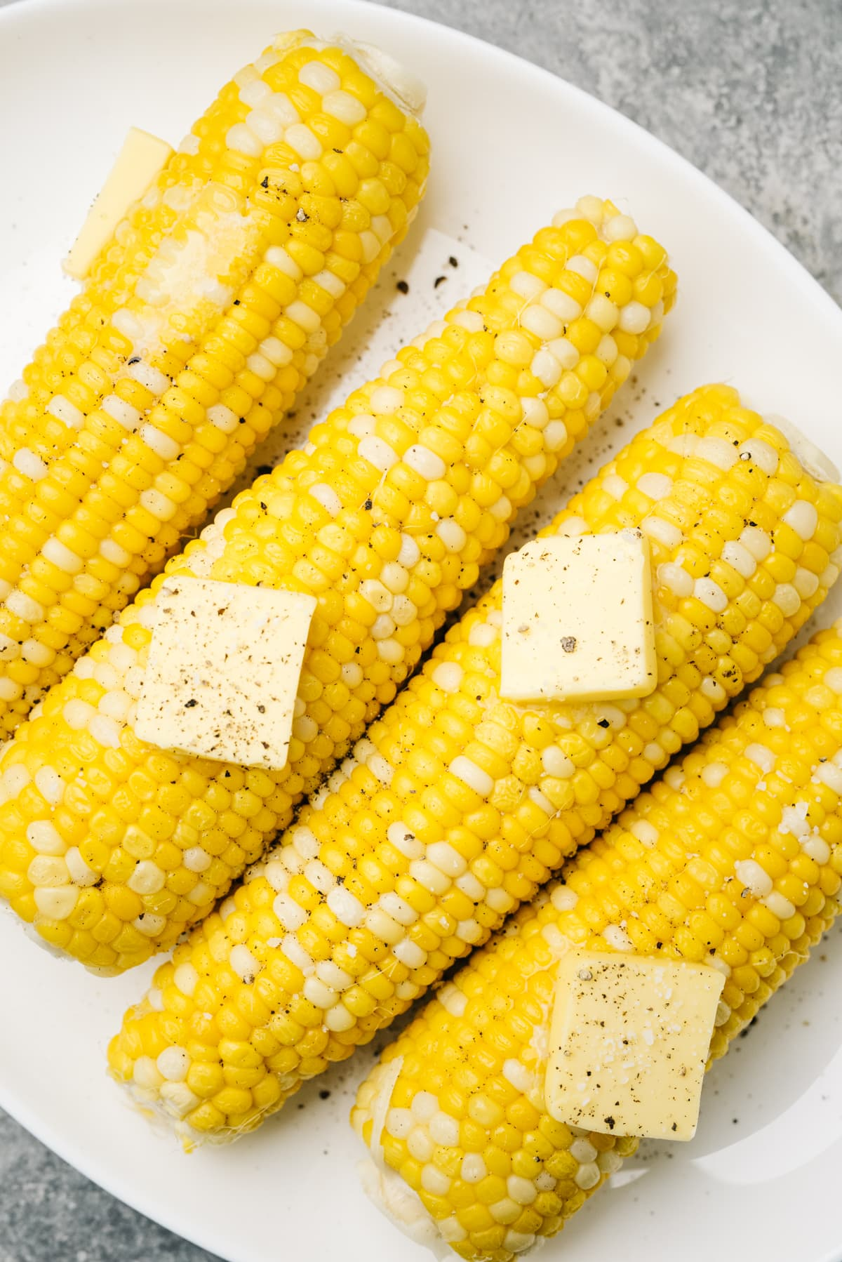 Four ears of boiled corn on a white plate, each topped with salt and one pat of butter.