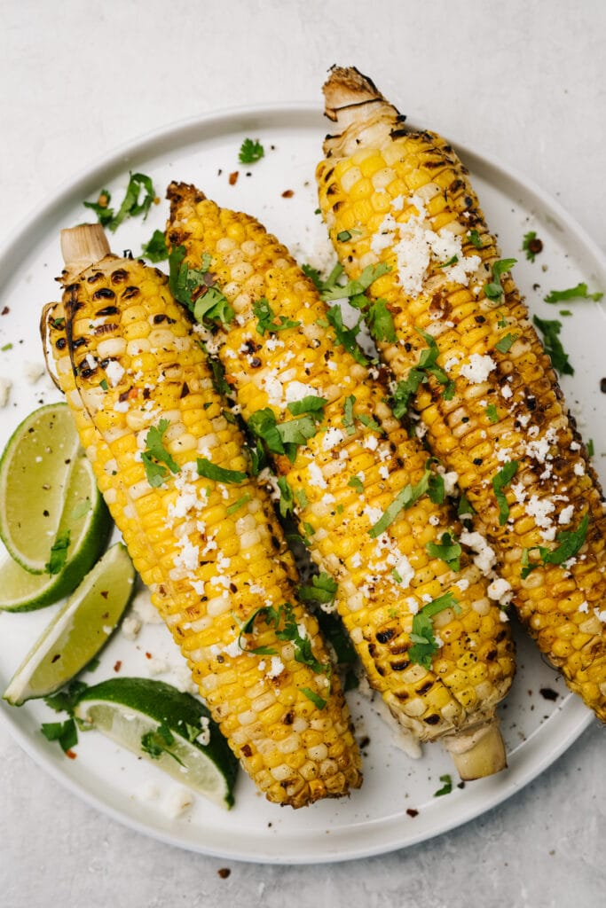 Three ears of grilled corn on the cob topped with lime juice, cilantro, and queso fresco cheese.