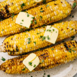 Four ears of cooked corn on the cob seasoned with butter and fresh herbs on a tan speckled plate.
