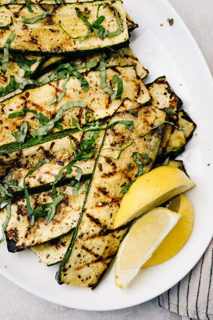 Grilled zucchini slices on a white platter with lemon wedges.