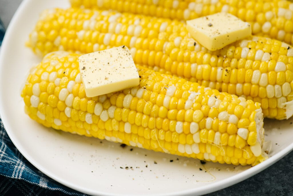 Side view, instant pot corn on the cob on a white plate topped with butter.