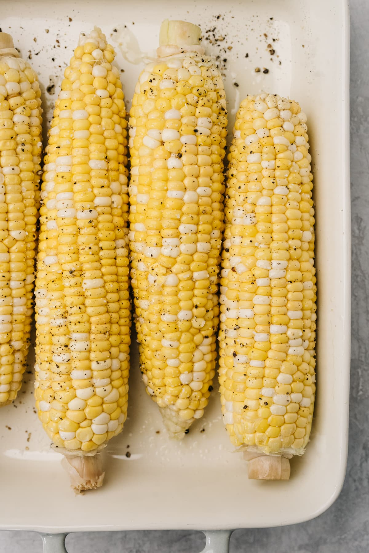 Four ears of corn with husks and silks removed, drizzled with olive oil, salt, and pepper, in a casserole dish.