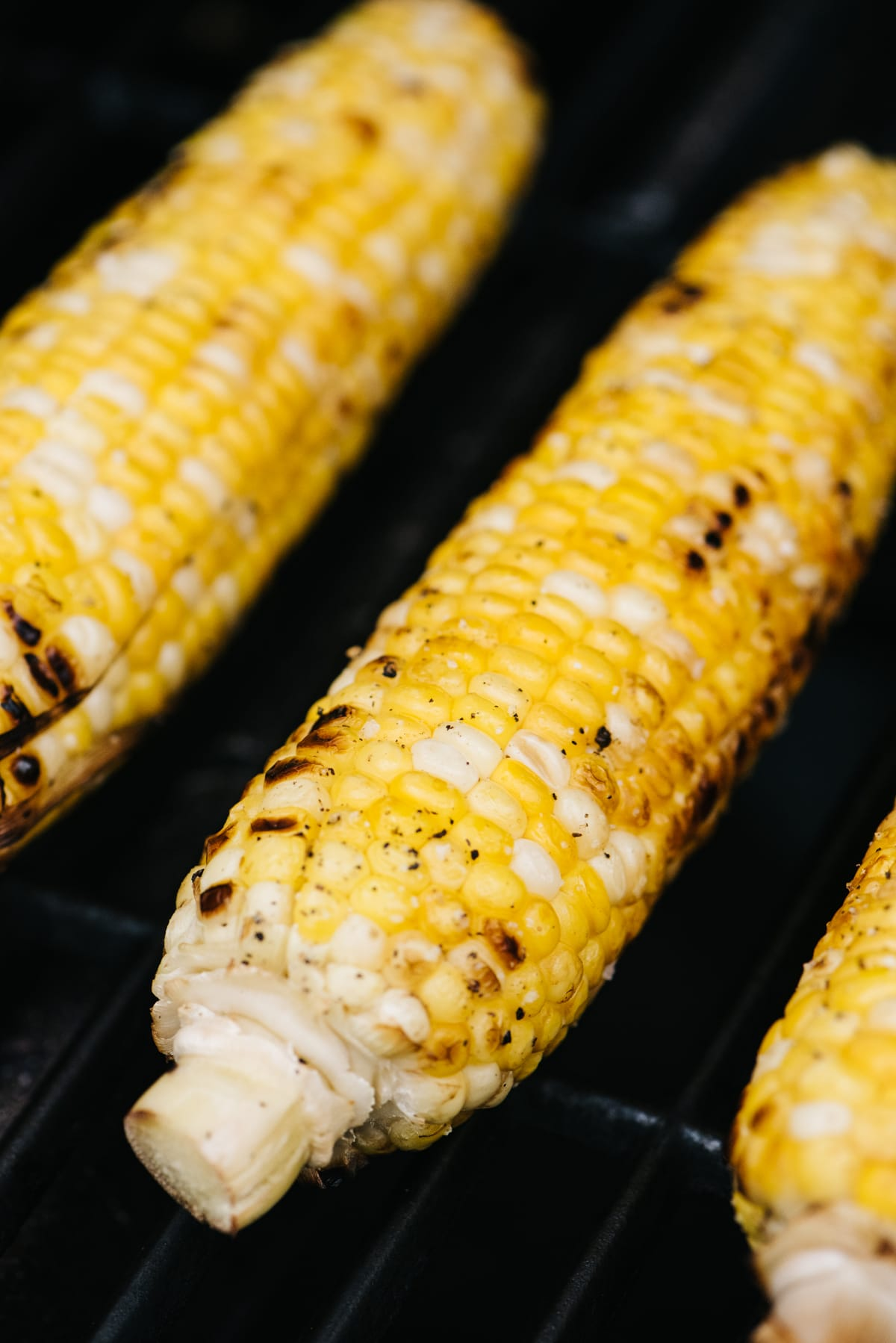 Corn on the cob with husks removed on a gas grill.