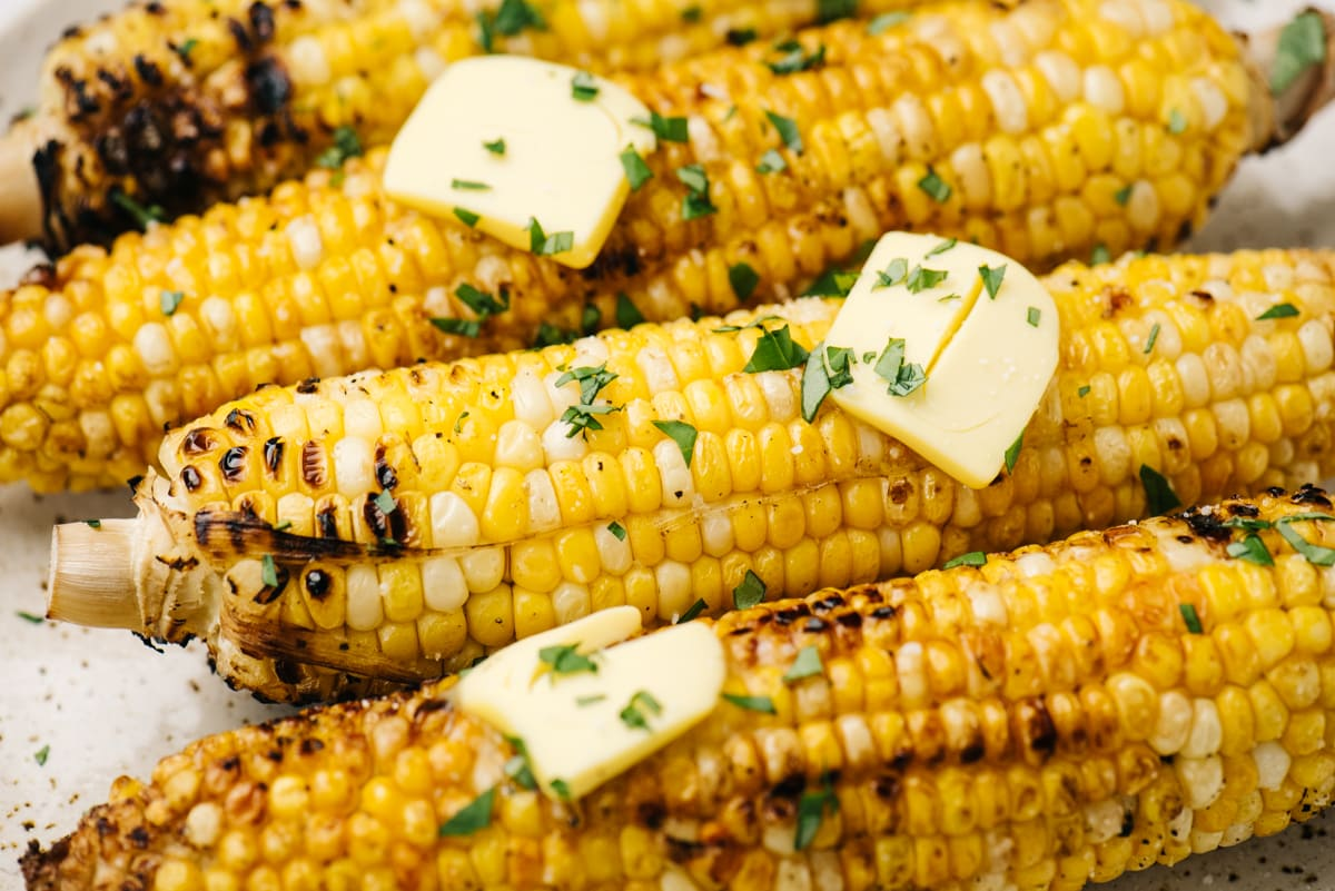 Side view, four ears of grilled corn on the cob topped with butter and chopped basil.