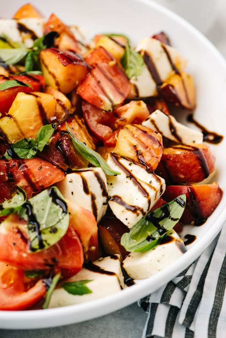 Side view, peach caprese salad drizzled with balsamic reduction in a white serving bowl.