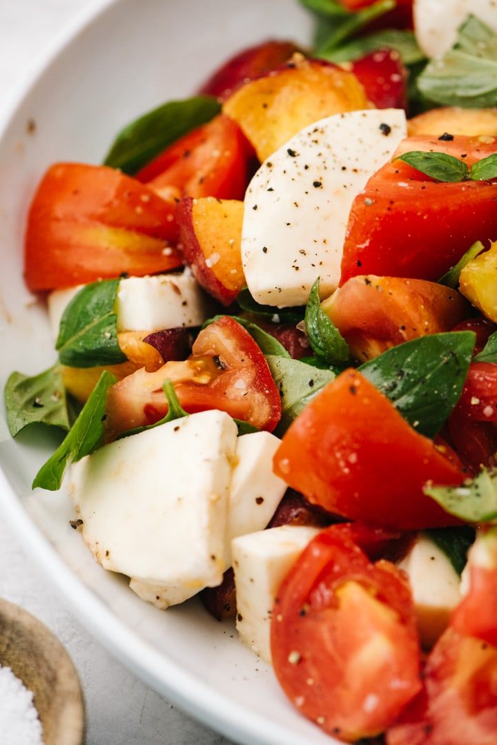 Side view, a peach caprese salad drizzled with olive oil and seasoned with salt and pepper.
