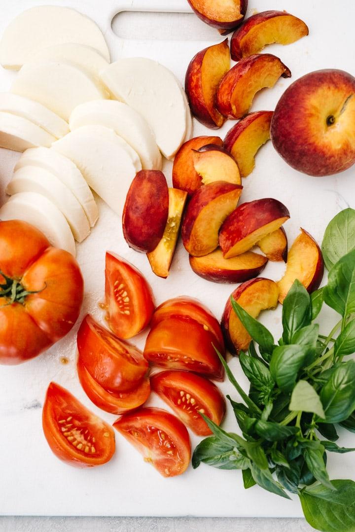 Sliced peaches, sliced tomatoes, sliced fresh mozzarella, and fresh basil on a white cutting board.