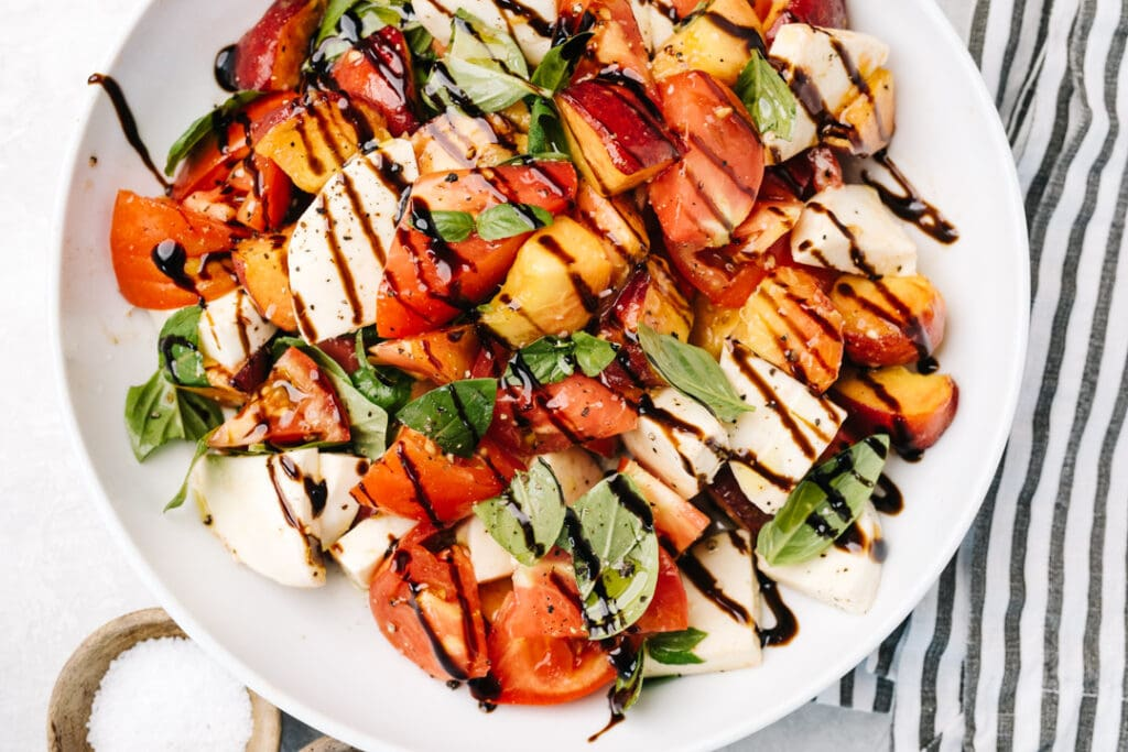 Peach caprese salad drizzled with balsamic reduction in a white salad bowl with a striped linen napkin..