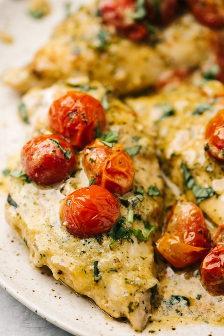 Side view, several chicken breasts in a creamy pesto sauce on a tan plate with burst tomatoes.