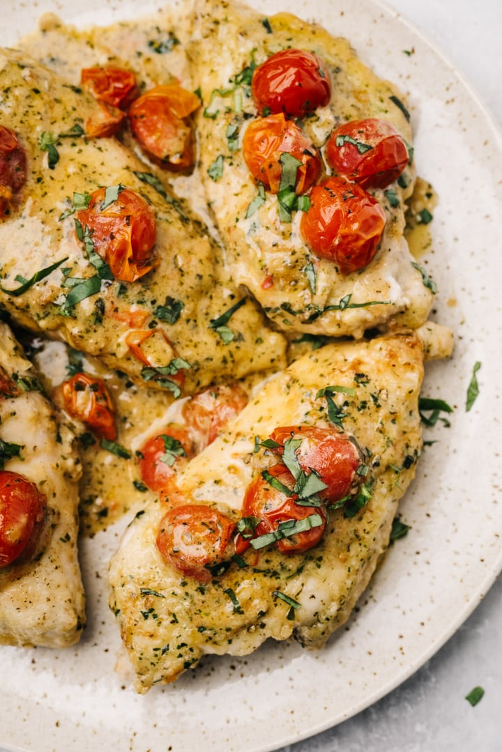 Creamy pesto chicken breasts on a tan plate, garnished with cherry tomatoes and fresh basil.
