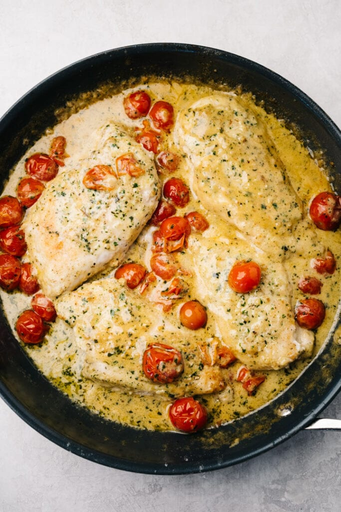 Pesto chicken breasts in a creamy sauce in a skillet with cherry tomatoes.