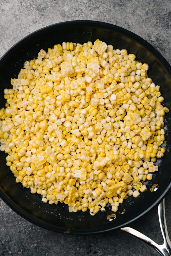 Raw corn kernels in a skillet.