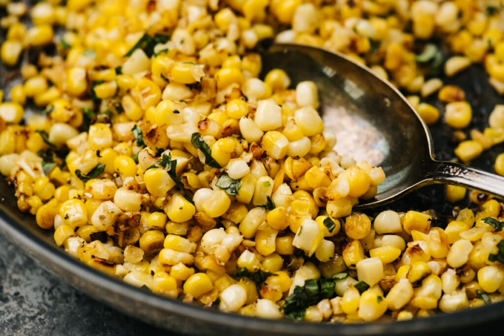Side view, sauteed fresh corn in a skillet with fresh herbs and a silver spoon.