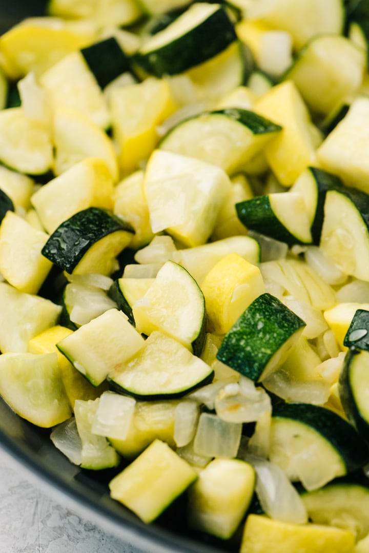 Side view, sautéed zucchini and squash with onions in a skillet.