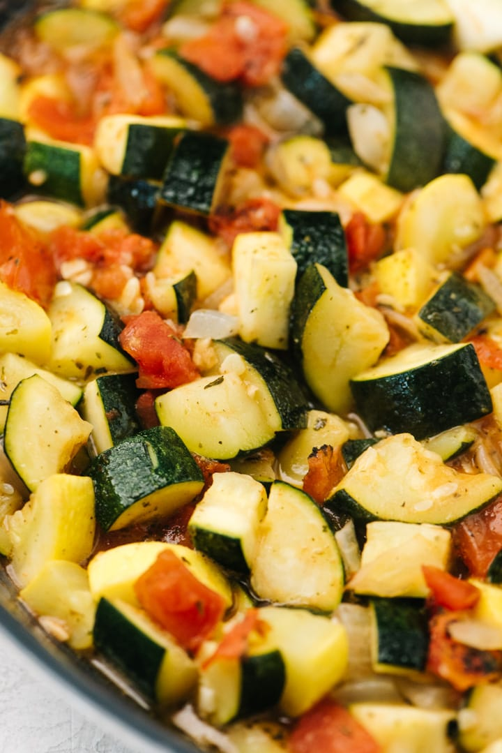 Side view, zucchini casserole vegetables sautéed in a skillet.