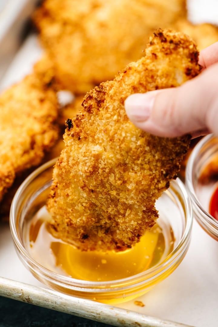 Dipping an air fryer chicken tender into honey.
