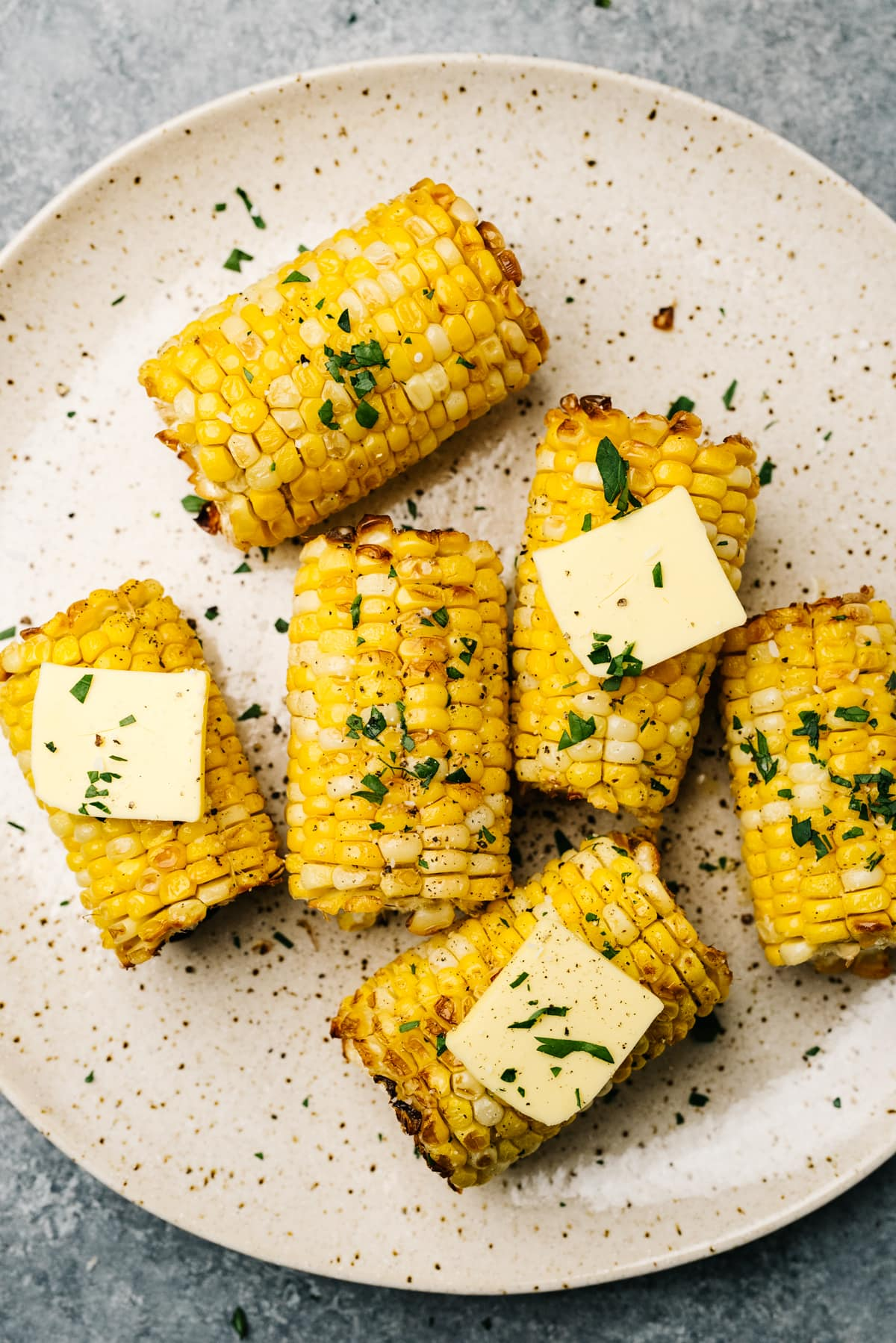 Corn on the cob cooked in an air fryer on a tan speckled plate, topped with butter and chopped fresh herbs.