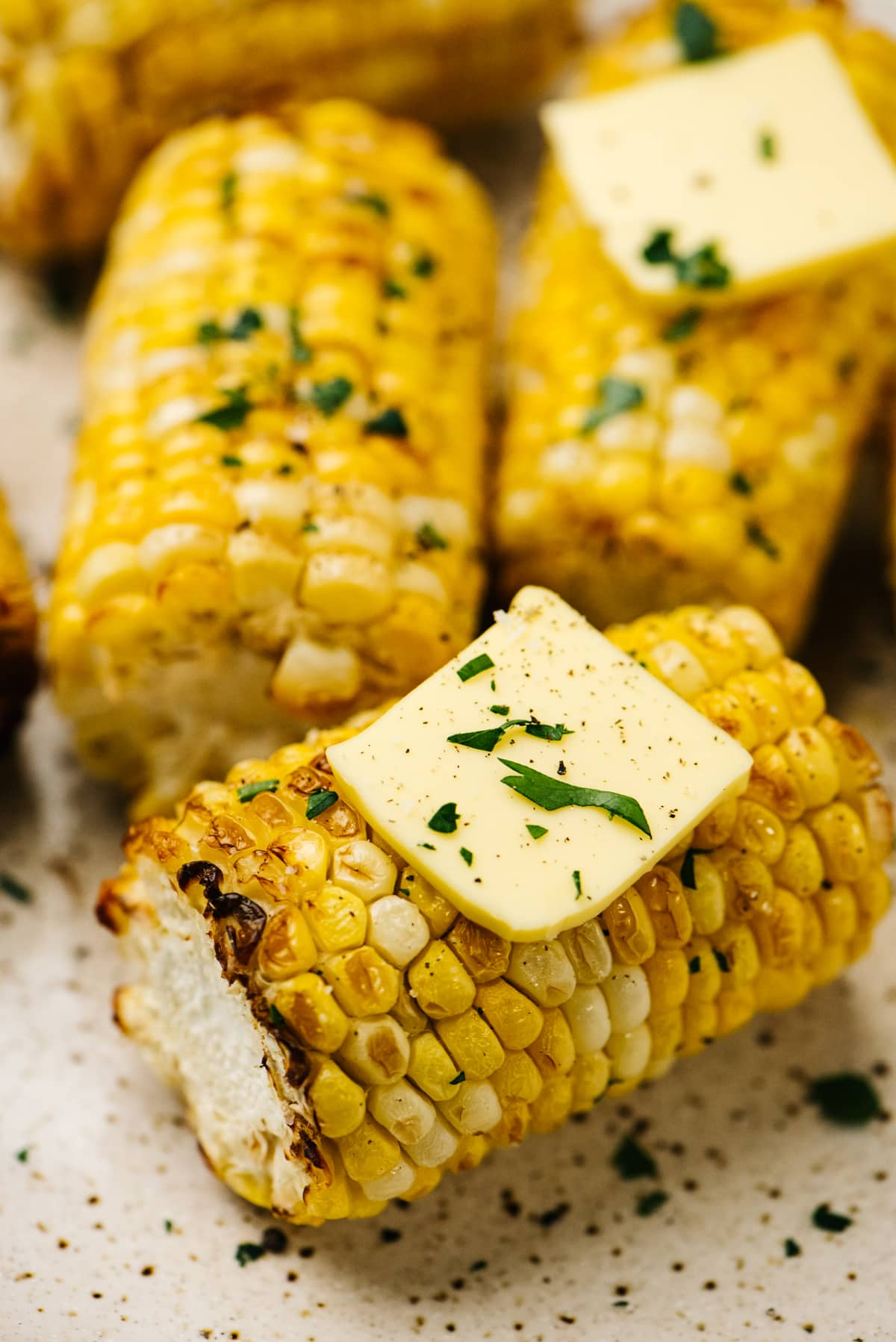Side view, air fryer corn on the cob on a speckled tan plate, topped with butter and chopped basil.