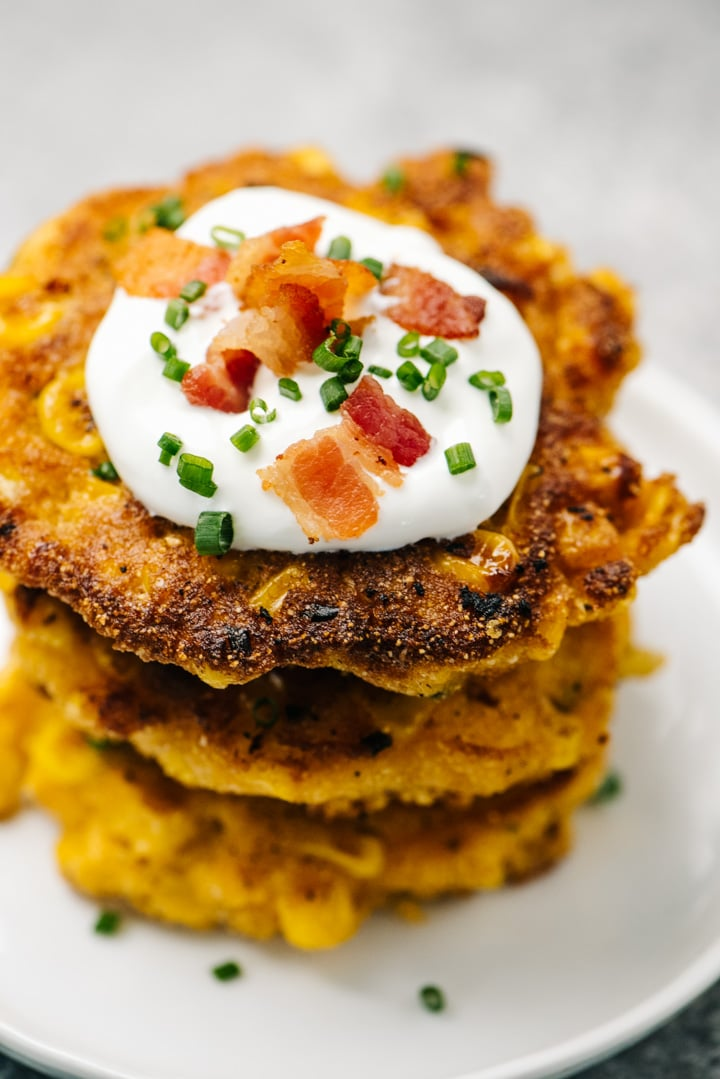 A stack of corn fritters topped with sour cream, bacon, and chives.
