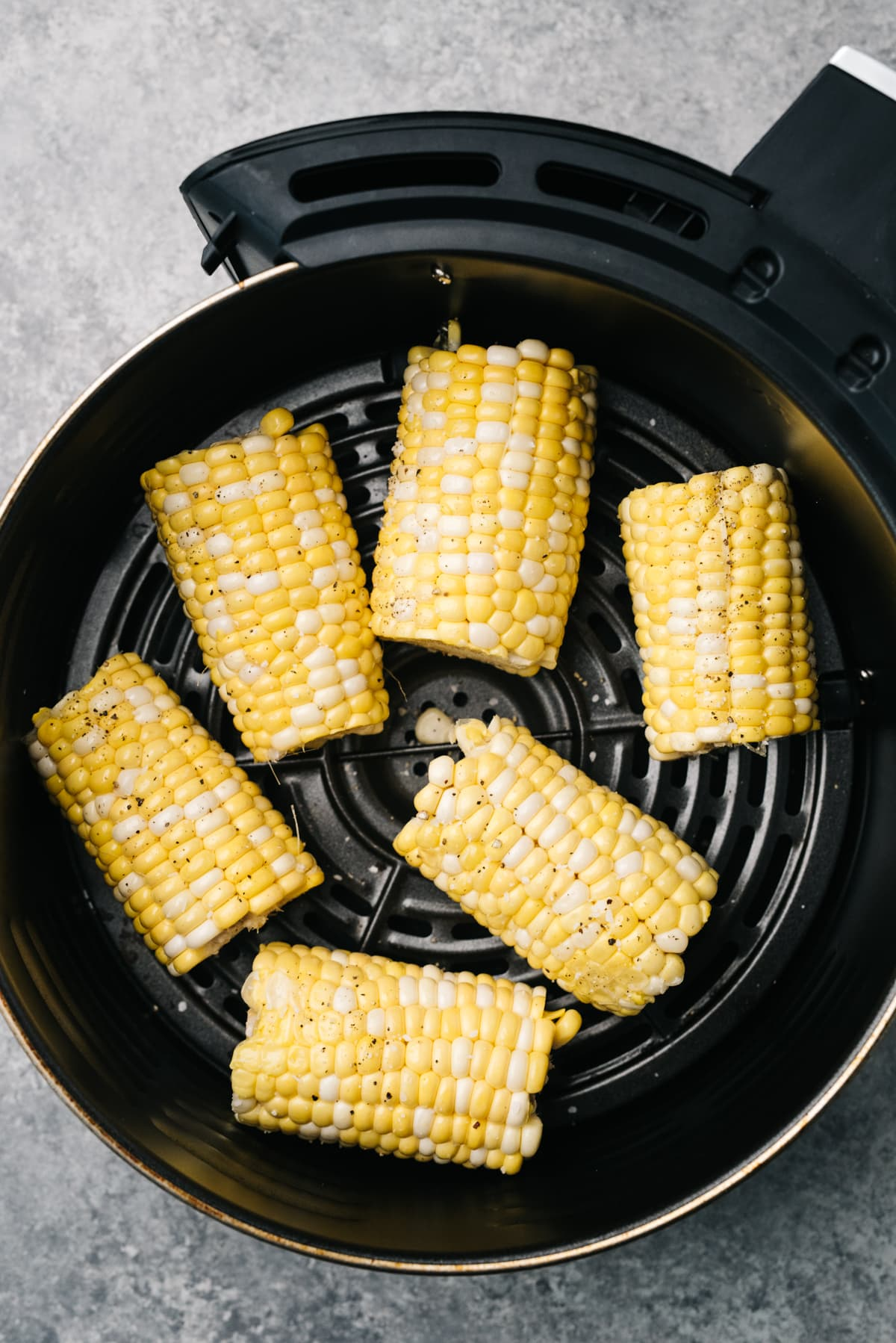 Raw pieces of corn on the cob rubbed with olive oil in the basket of an air fryer.