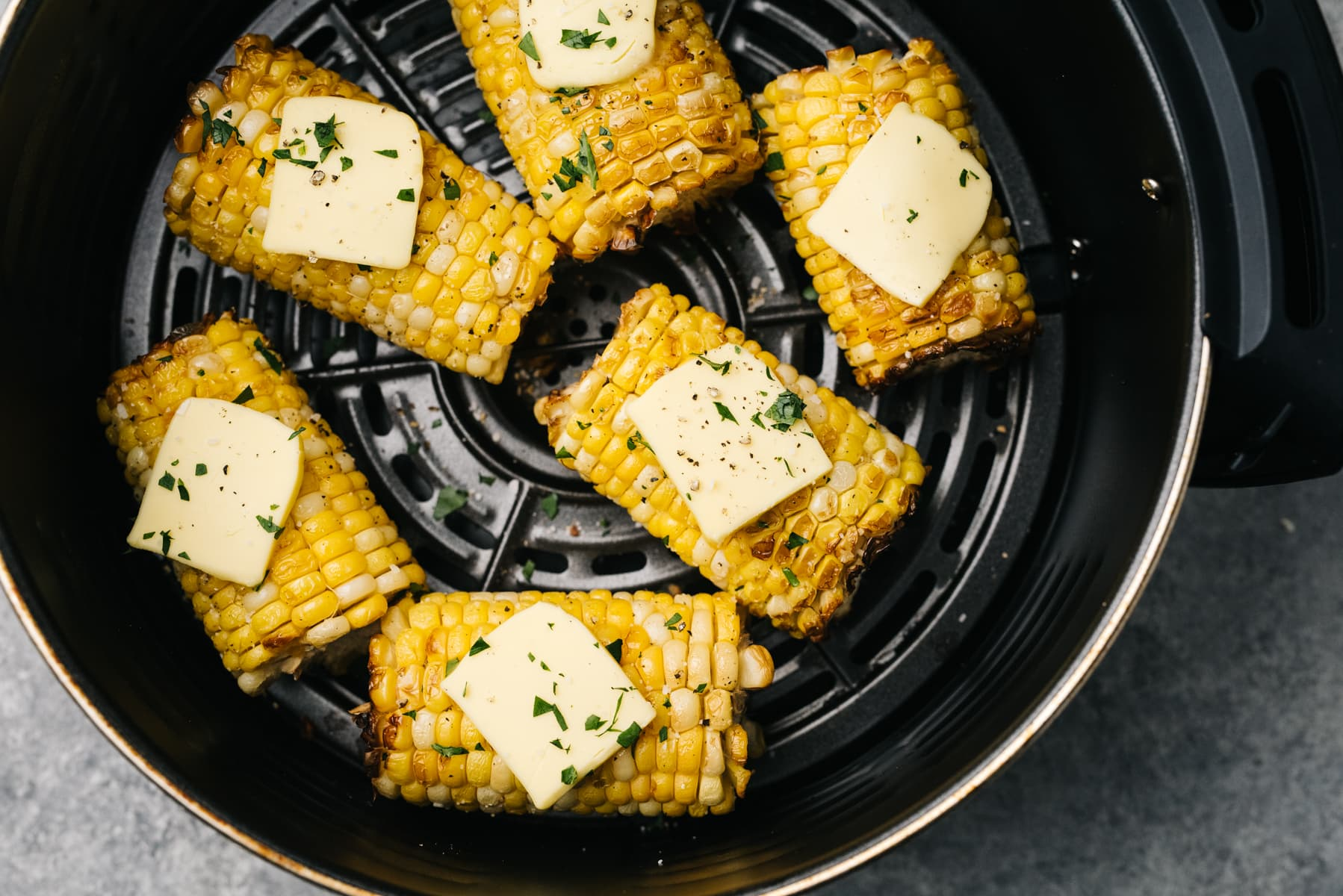 Air fryer corn on the cob in the basket of an air fryer, topped with butter and chopped basil.