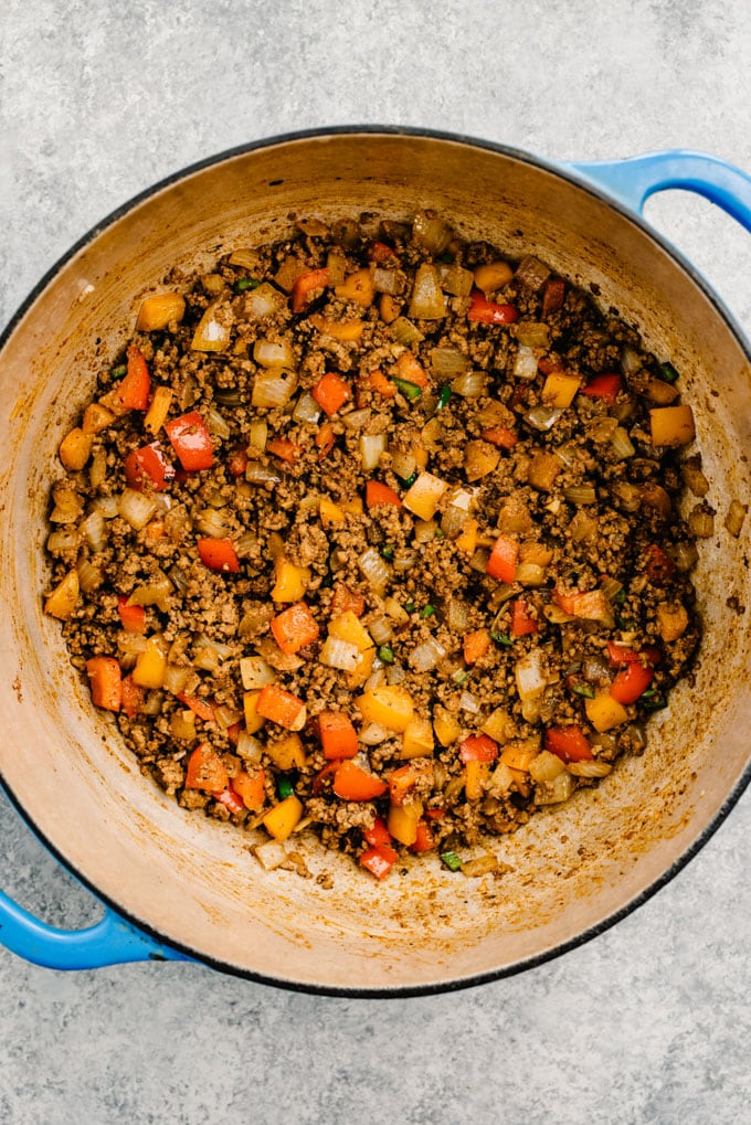 Ground beef and vegetables seasoned with taco seasoning, garlic, and jalapeno in a blue dutch oven.