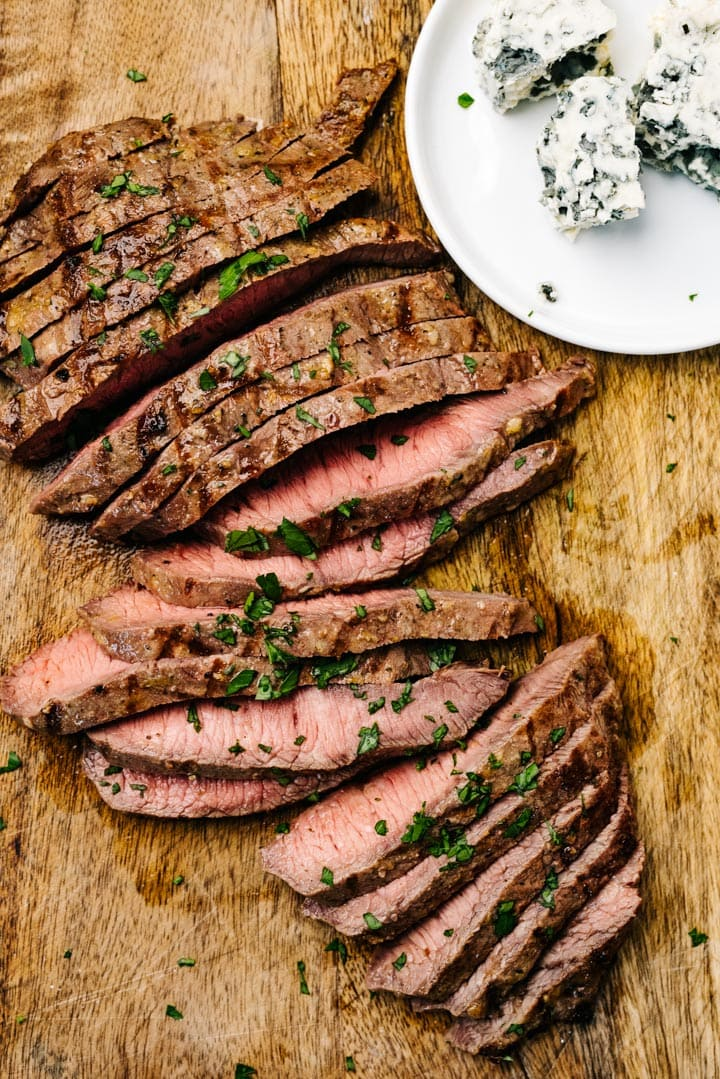 Thin slices of flat iron steak on a cutting board with crumbled blue cheese on the side.