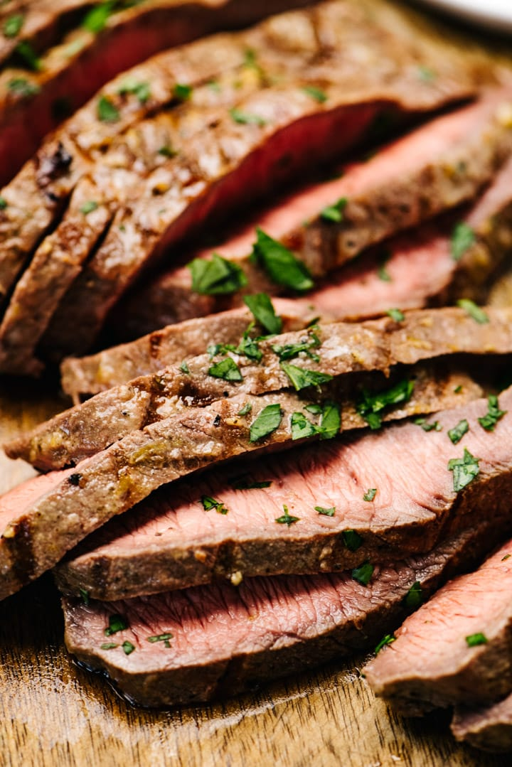 Thin slices of grilled flat iron steak on a cutting board.