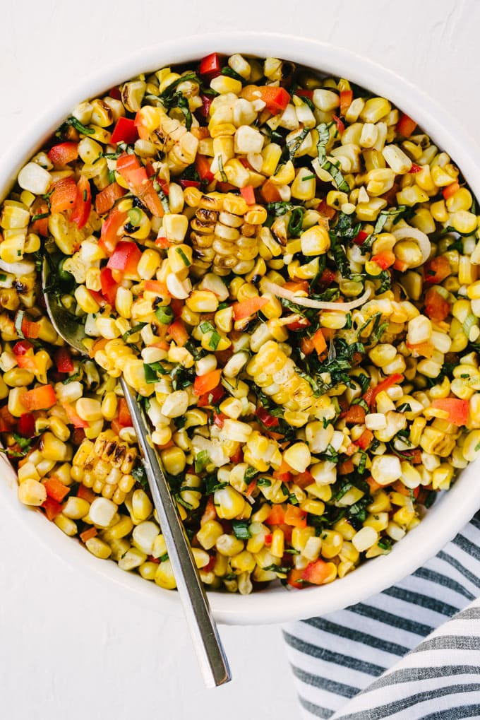 Grilled corn salad in a white serving bowl with a silver serving spoon and striped linen napkin.