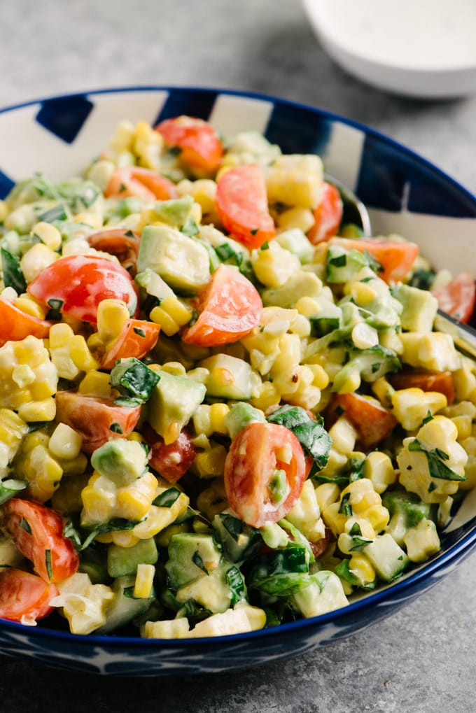 Side view, corn and tomato salad in a blue and white bowl on a cement background.