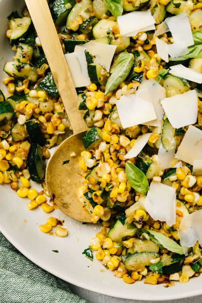 Sautéed zucchini and corn in a tan serving bowl with a gold serving spoon.