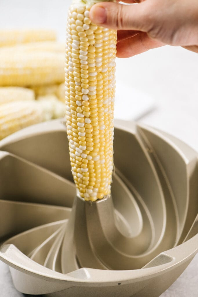 An ear of corn standing upright in the center of a bundt pan.