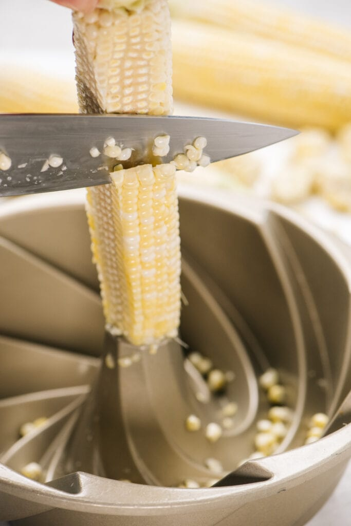 Running a chef's knife along an ear of corn standing upright in a bundt pan to slice off the kernels.