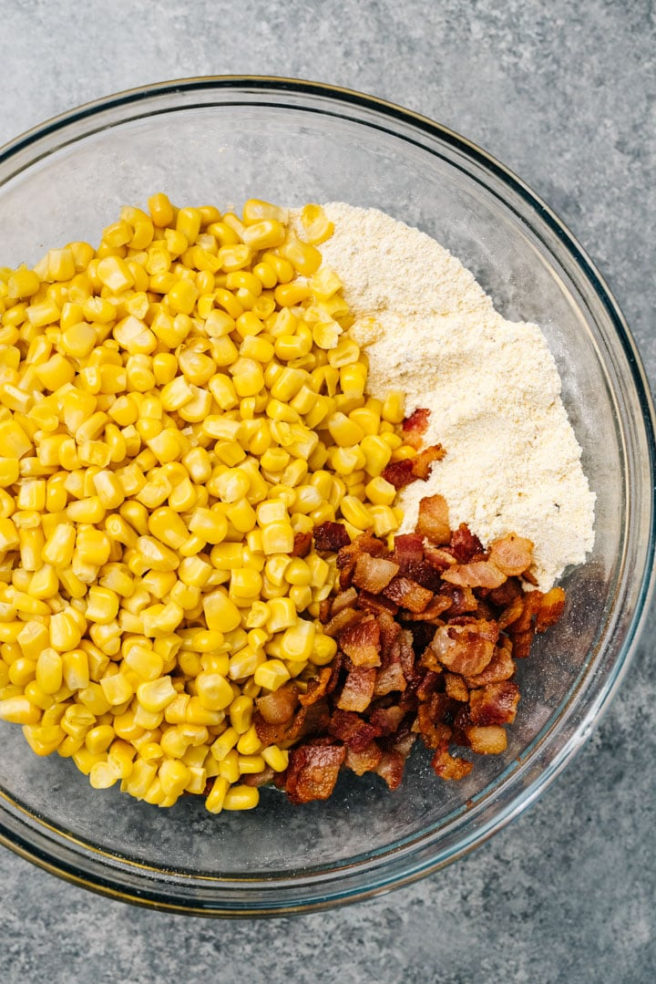 Corn kernels, cooked bacon, cornmeal, and seasonings in a large glass mixing bowl.