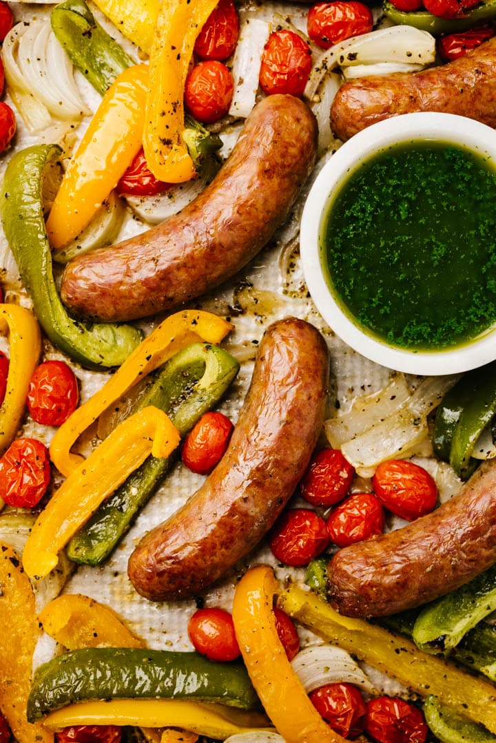 Sheet pan sausage and peppers on a baking sheet with a small bowl of basil sauce on the side.