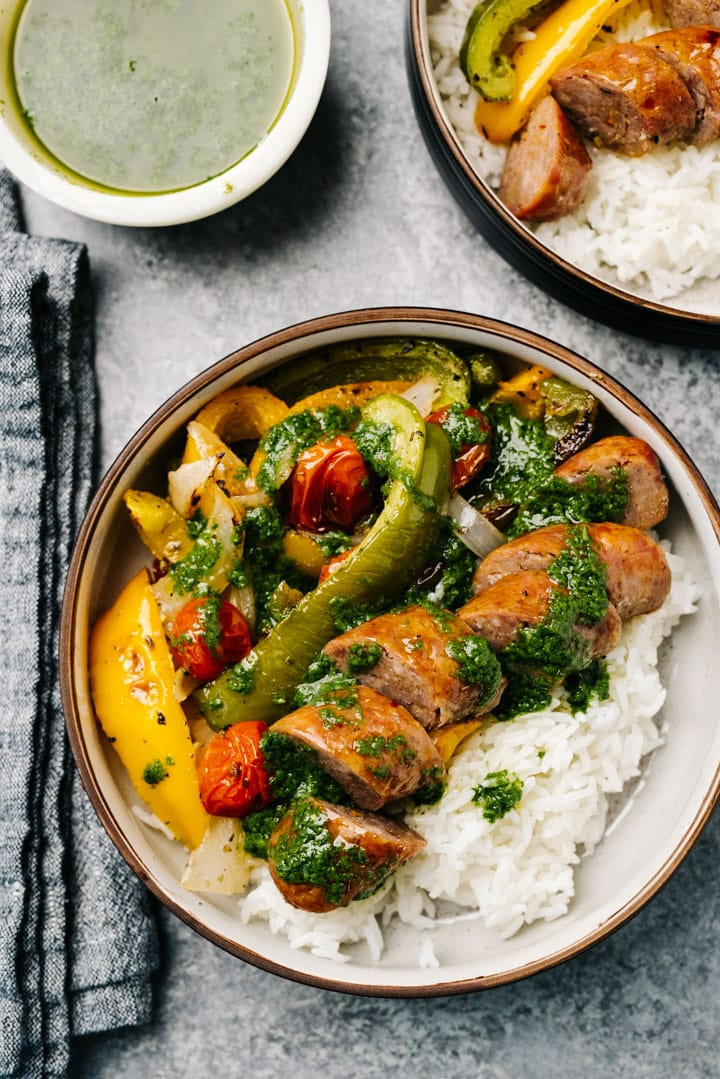 Two bowls of sheet pan sausage and veggies over white rice, topped with fresh basil sauce.