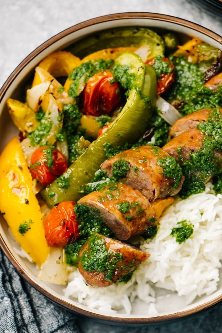 Sheet pan sausages with veggies in a serving bowl over white rice, drizzled with basil sauce.