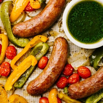 Cooked sausages, peppers, and tomatoes on a sheet pan with a small bowl of basil sauce on the side.