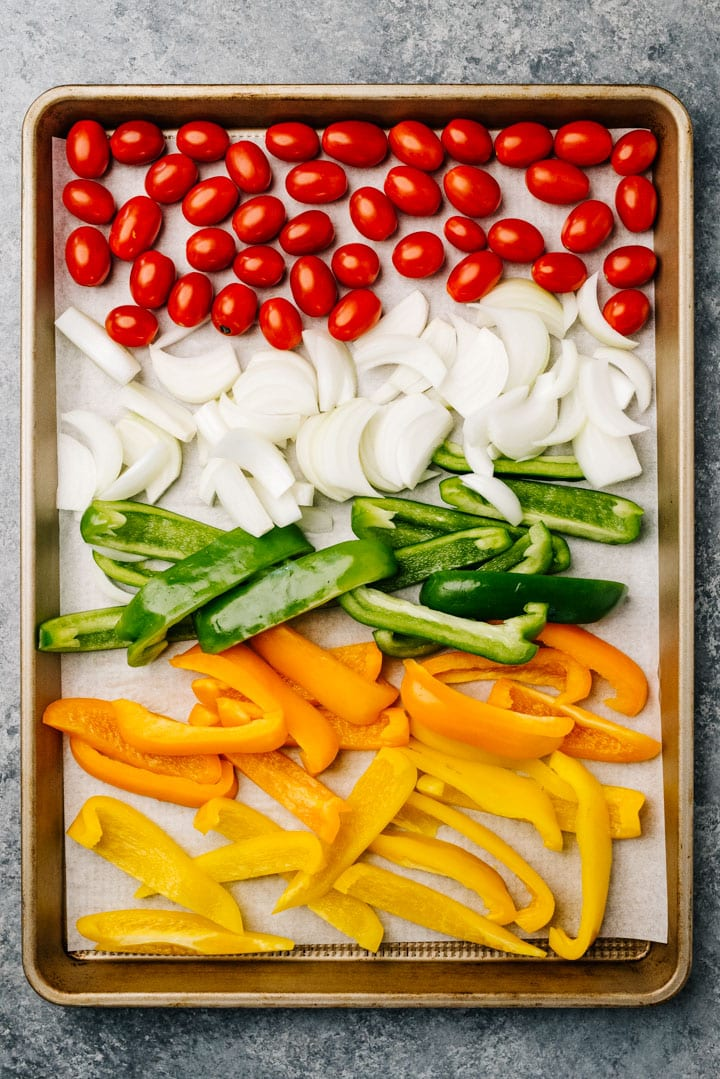 Cherry tomatoes, sliced onions, and sliced bell peppers arranged on a sheet pan.