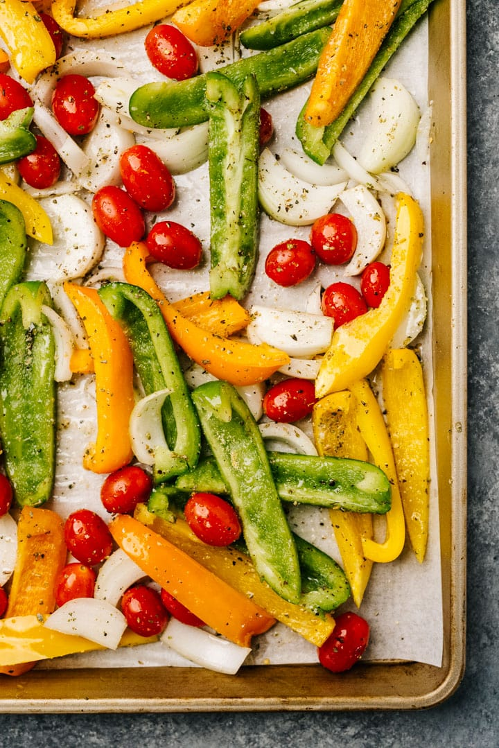 Cherry tomatoes, onions, and bell peppers tossed with olive oil and seasonings on a sheet pan.