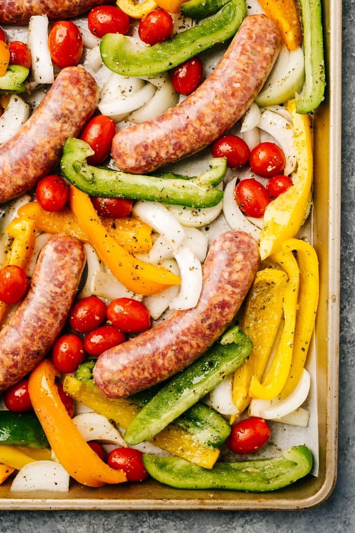 Raw italian sausage links nestled with veggies on a sheet pan.