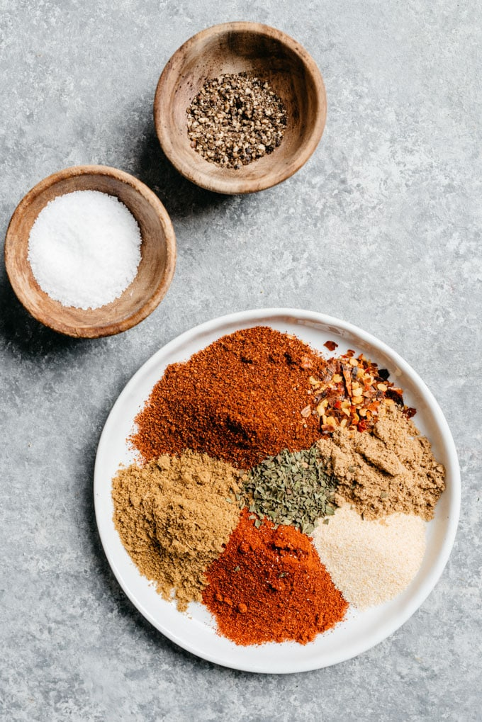 The ingredients for homemade taco seasoning arranged on a concrete background.