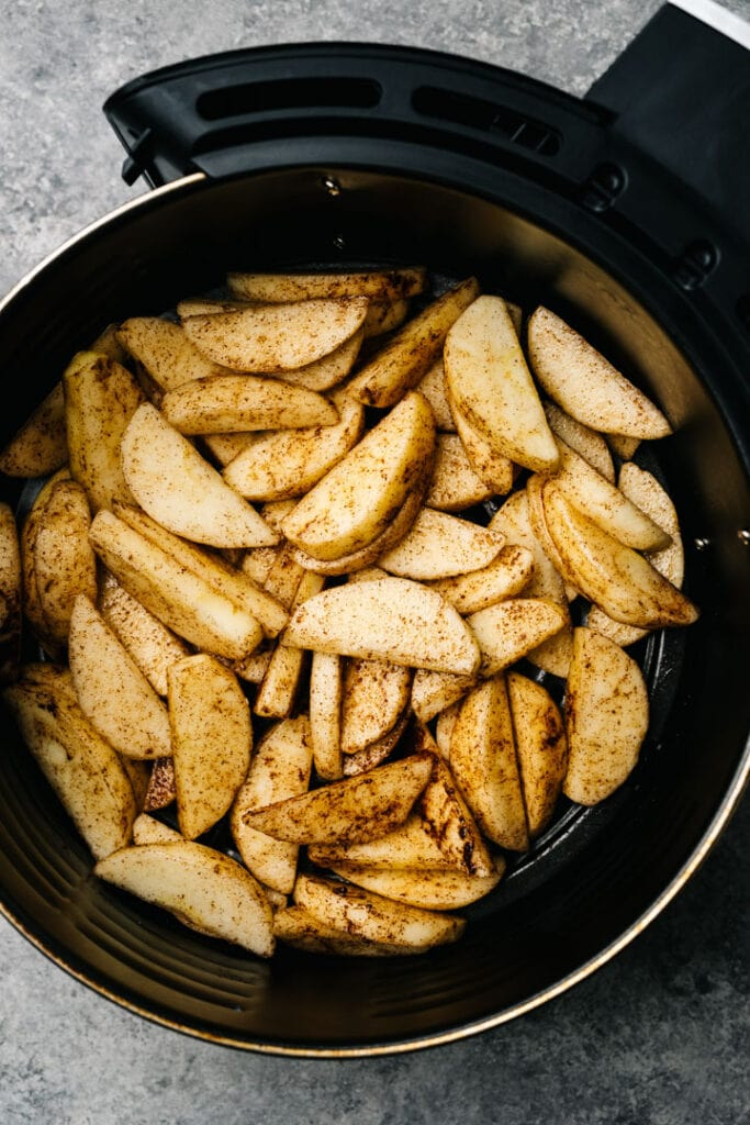 Raw apple slices tossed with olive oil and cinnamon in the basket of an air fryer.